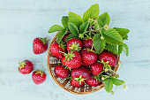 a bowl of red juicy strawberries on white wooden table. Healthy and diet snack food concept.