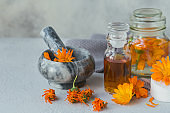 Calendula products. Bottle of cosmetic, aromatic or essential oil and fresh and dry calendula flowers on light background. Aromatherapy, spa and wellness concept