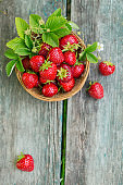 Fresh strawberries in a basket on rustic wooden background top view. Healthy food on wooden table mockup. Delicious, sweet, juicy and ripe berry background with copy space