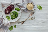 Healthy breakfast with boiled beetroot, spinach leaves and sesame seeds on white wooden table.