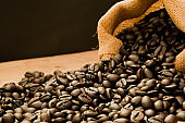 coffee wallpaper, closeup dark brown roasted coffee beans background and coffee sack bag on wooden table for the coffee shop background lifestyle idea with copy space