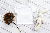 Blank gender neutral white baby bodysuit close up - with toy and dried branch