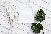 Blank gender neutral white baby bodysuit close up - with toy and plant