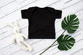 Blank gender neutral black baby bodysuit close up - with toy and plant