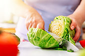 Chef slicing vegetables and cabbage on the table in restaurant. Process of cutting and preparation food in kitchen.