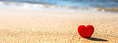 Romantic symbol of red heart on the sand beach