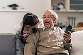 elderly man with granddaughter using mobile phone together