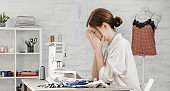 Sleepy, frustrated, exhausted seamstress with headache on her work desk. Small business or self-employed problems. Deadline or overwork concept, bored or getting tired at work in creative industry.