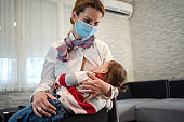 Mother breastfeeding child at home in isolation