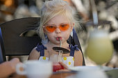 Fashionable 3 years old girl drinking juice with metal reusable straw