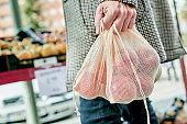 man using a reusable mesh bag at a greengrocer