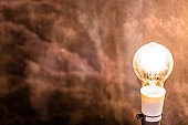 Old dusty light bulb shining light against blurred decaying wall with copy space