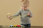 Adorable blonde toddler girl playing with adhesive paper tape, childhood and creativity concept