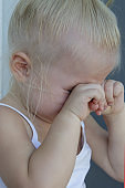 Close up candid portrait of upset crying toddler girl covering eyes with hands