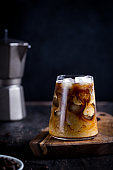 cold latte coffee drink with ice. Ice coffee on a wood table with cream being poured into it showing the texture