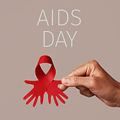 man holding a red ribbon and text aids day
