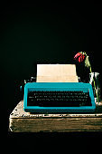 old typewriter and a wilted red rose