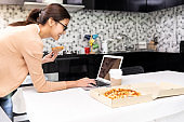Asian woman work from home with take out food.