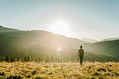 A young tourist man with a backpack on top and enjoying the sunset. Back view. Hipster walks in the autumn grass in the mountains on vacation. Holiday trip concept. World Tourism Day.
