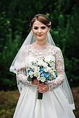 Portrait attractive bride in a wedding dress standing with bouquet of flowers on the background of greenery. Nature, country. Stylish blue wedding.