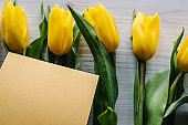 Craft postcard on yellow tulips on wooden background. Space for message. Concept Hello Spring flowers. Holiday greeting card for Valentine's, Women's, Mother's Day, Easter! Top view, flat lay.