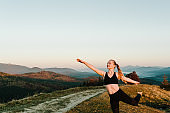 Meditation. Woman balanced, practicing meditation and zen energy yoga in mountains. Girl doing fitness exercise sport outdoors in morning. Healthy lifestyle concept. Sunrise. Side view.