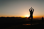 Silhouette woman balanced, practicing meditation, zen energy yoga in mountains. Healthy lifestyle concept. Young girl doing fitness exercise sport outdoors. Morning sunrise. Relax in nature. Back view