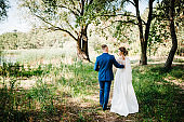The groom and bride walking in the country. Portrait of the newlyweds in the park. Happy couple. Wedding photo. Couple in love. Back view.