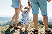 Mom, dad and daughter in the mountains enjoy and look at nature. View back down. Bottom view of legs. Young family spending time together on vacation, outdoors. The concept of family summer holiday.