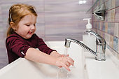 Prevention of Coronavirus, flu disease. Child, kid wash hands with antibacterial soap, warm water rubbing nails and fingers in sink. Washing hands and hygiene. Covid-19. To stop spreading coronavirus.