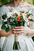 The bride holds a wedding bouquet outdoors. Close up.