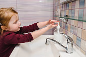 Washing hands and hygiene. Prevention of Coronavirus, flu disease. Child, kid wash hands with antibacterial soap, warm water rubbing nails and fingers in sink. Covid-19. To stop spreading coronavirus.