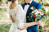 Bride holds a wedding bouquet. Wedding dress, wedding details. Groom hugs bride. Love.