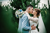 Happy bride and groom kissing after wedding ceremony on nature. Couple newlyweds on the background greenery.