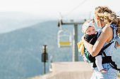 Carrying a baby. Young mother with her daughter in sling. Portrait of happy family. Mom and girl in mountains in nature. The concept of summer holiday.