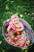 Cute little baby girl sitting in a basin on the nature and bathed in summer. Happy girl playing peach and apples in bath in the garden.