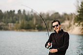 Fisherman with rod, spinning reel on the river bank. Man catching fish, pulling rod while fishing from lake or pond with text space at weekend. Fishing for pike, perch, carp on beach lake or pond.