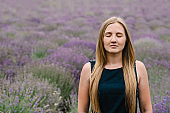 Beautiful girl in dress in purple lavender field. Beautiful woman walk on the lavender field. Girl collect lavender. Enjoy the floral glade, summer nature. Natural cosmetics and eco makeup concept.