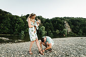 Husband helps to put on shoes to wife, who holds little girl. Holidays, vacations, family support.