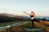 Meditation. Woman balanced, practicing meditation and zen energy yoga in mountains. Girl doing fitness exercise sport outdoors in morning. Healthy lifestyle concept. Sunset.