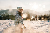 Girl enjoys the snowy winter mountains. Walk in nature. Frost season. Holidays concept. Trekking in mountains. Cold weather, snow on hills. Hiking. Mountaineer on the top in a sunny winter day.
