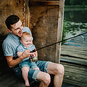 Father with daughter sitting on wooden pier and catching fish on lake background. Family fishing together on pond. Family fishing holiday. Young dad with child outdoors near river in summer.