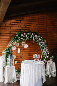 Arch for wedding ceremony a is decorated with white flowers and greens, greenery. Photo-wall, space or place on the background of wooden wall. Wedding decoration on boho style: Dream catchers.