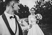 Romantic wedding moment. Couple of newlyweds walking in the park. Wedding ceremony in nature. Black and white photo.