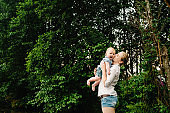 Young mother kissing baby girl walk in park. Family holiday in garden. Portrait mom with child together on nature. Mum, little daughter outdoors. Happy Mothers Day. Close up.
