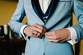 Man fastens the buttons. The groom in a suit, shirt standing in room. Close up.