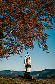 Meditation. Woman balanced, practicing meditation and zen energy yoga in mountains. Girl doing fitness exercise sport outdoors in morning. Healthy lifestyle concept. Sunrise.