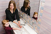 Washing hands. Stop spreading coronavirus. Preventive measures against Covid-19 infection. Mom tells child how to wash her hands with antibacterial soap properly, warm water rubbing nails and fingers.