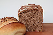 Close-up of an already cut bread and two buns on a wooden table with white background and copy-space