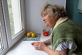 Thoughtful elderly woman at home in the kitchen looking out the window.